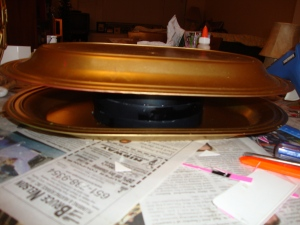 I glued several ice cream pint lids that I'd spray-painted black into a stack and then glued each of the platters to the top and bottom of that stack to form the shoulders/upper torso of Crow.